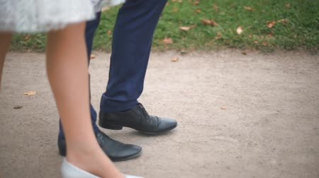two hearts : Legs of newly married couple walk in autumn park.