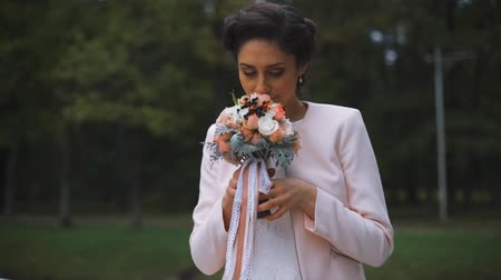 contato com os olhos : Middle shot of hands young stylish bride with a beautiful bouquet of flowers in the park. Sniffing.