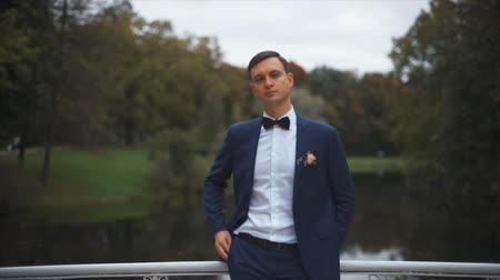 celebrity : Close up portrait of handsome stylish groom outdoors in park with dark red bowtie