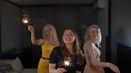 Бенгалия : Three young attractive handsome sexy ladies happy dancing with Bengal light. They smiling and have a lot of fun at home flat apartment birthday party. Super slow motion.