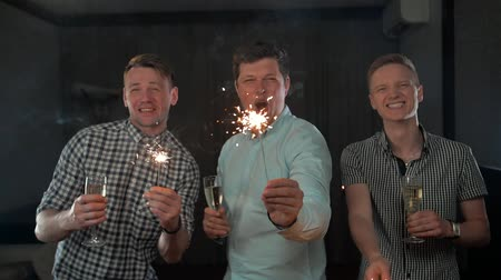 Бенгалия : Happy New Year Celebrating Handsome Young Men Holding Sparkles. Slow motion middle shot. Big home apartment party. Socialite. Dark background