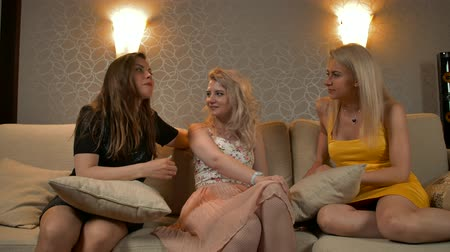 pletyka : Three young sexy  women speaking and gossiping at home party. They smiling discussing their fellow husbands, boyfriends, colleagues from work. Stock mozgókép