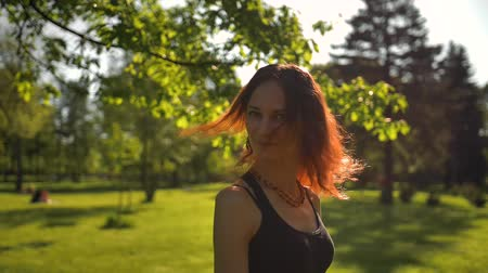 coquettish : Beautiful, attractive young red-haired girl enjoys nature and fresh air, then turns around and laughing and looking very cheerful and happy. slow motion Stock Footage