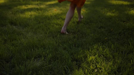 polního : Ladys feet running by grass in park. No face. Sunset or surise. Real-time and slow motion mixed footage. Middle skirt, slender legs, barefoot.