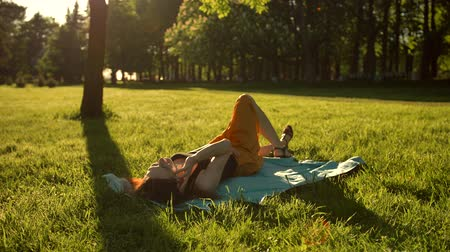 repousante : Pretty girl lying down on a meadow and talking by smartphone. Female flip over from belly to back. She very happy of conversetion vith friend. Sunrise.