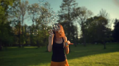 arejado : Beautiful young redhair woman blowing soap bubbles outdoors. Slow motion shot of childhood time in adult age. Fun under the rays of the sun. Smooth camera movement. Vídeos