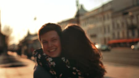 A male meeting a female walking down the street and ggiving her a hug, close up. Slow motion evening sunset footage. Turn around.