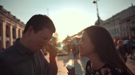 ırklararası : Happiness couple with ice cream under sunlight. They joking smearing noses in ice-cream. Smiling, laughing and having fun. Slow motion. Stok Video