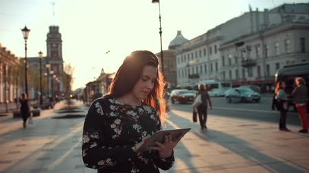 beatiful : Young girl with tablet surfing Internet on city street at evening sunset. She try to find something interesting. Crowd of people at background Stock Footage
