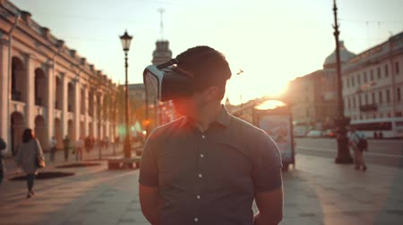 zajímavý : Guy in vr glasses in city trying to find something interesting additional information of this place. Virtual reality concept. Sunset or sunrise.