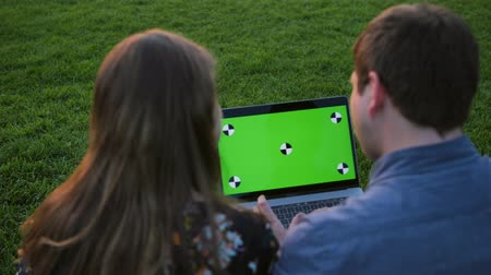 ödev : A happy couple using notebook with green screen. Man and woman using laptop outdoors. Happy couple on the meeting or date looking on the computer screen smiling.