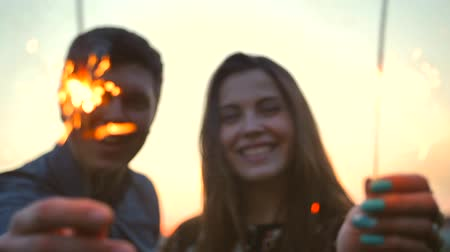 cintilante : The couple dancing with firework sticks on an morning sunrise background. Super slow motion. Close-up of fireworks and sparklers. Re-focusing from sparklers to faces. Stock Footage