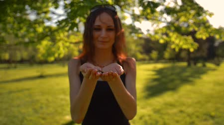 смелый : Young woman blow colorful glitter confetti outdoors in sunrise park. She happy of her carefree lifestyle timespending. Super slow motion.