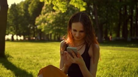 conectado : Happy Smiling Young Woman enjoying Nature and sunrise. Sitting on bench in green summer park using mobile. Cheerful female talking on her mobile, chatting with friends on smartphone. Middle shot.