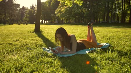 küçük kız : Happy young adult attractive female laying down over green grass while typing a message on phone and swing legs with joy. Stok Video