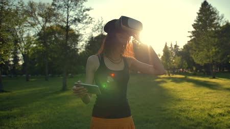 goggles : Beautiful caucasian woman enjoy virtual reality walking on grass in park. VR headset glasses device. nature outdoors background. people and technology concept. Sunset or sunrise natural lighting. Stock Footage