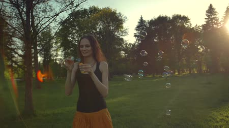 puffing : Young woman playing with soap bubbles, outdoor having fun. Sunflare.  Super slow motion middle shot.