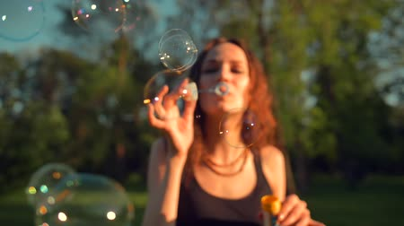 hůlky : Happy Smiling Woman Enjoying Nature. Standing in summer park. Front view of Young pretty adult girl making soap bubbles. Beautiful tree with leaves on background in slow motion. Close-up