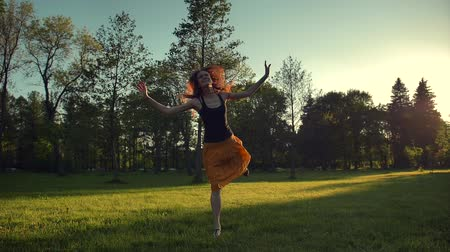 zmysłowy : Attractive female in long red skirt jumping and dancing outdoor in a park. She happy of enjoying time spending. Sunrise or sunset beautiful light. Super slow motion shot.