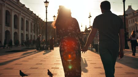 Outdoor lifestyle portrait of young couple, guy and girl in love walk in city on the street behind sunset. Wideo