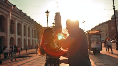 A beautiful couple dancing an dance with elements of waltz, leaks of sun. City background with cars and transport. blurred people. Wideo
