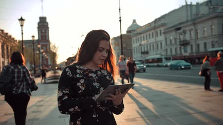 horas : Young attractive hansome redhai girl with tablet surfing Internet on city street at evening sunset. She try to find something interesting. Crowd of people at background.