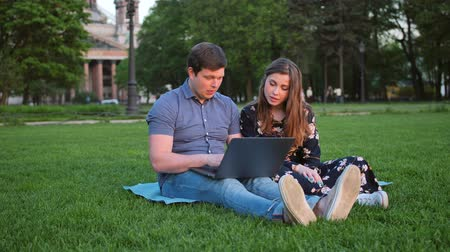 coreano : Young Beautiful Couple Looking at Laptop and Laughing, Sitting in Park in Summer with Amazing Sunlight Stock Footage