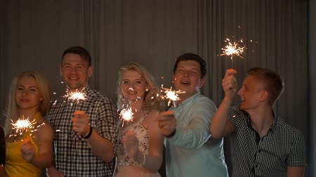 flet : Party with friends. Group of cheerful young people carrying sparklers. They hugging, smiling, laughing.