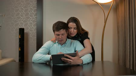 two rows : Attractive couple surfing on tablet in home. Woman hugging man and getting him internet shopping advices. Stock Footage