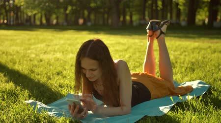 looking down : Happy young adult woman laying down over green grass while typing a message on phone. Legs swinging Middle shot.