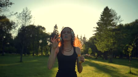 hůlky : Young woman playing with soap bubbles, outdoor having fun. She walking in green summer evening sunset park. Super slow motion shot.
