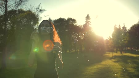 relaks : Redhair retty lady playing with soap bubbles, outdoor having fun. She walking in green summer sunrise or sunset park. Slow motion.