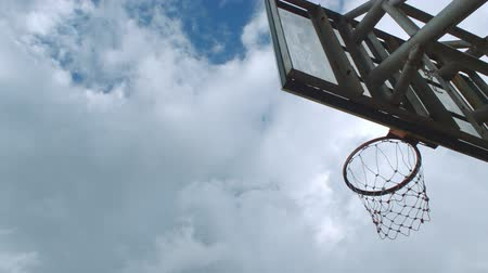 Basketball hoop with blue sky background, time lapse.