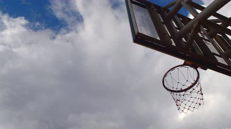 Basketball hoop with blue sky background, player playing basketball moment. Стоковые видеозаписи