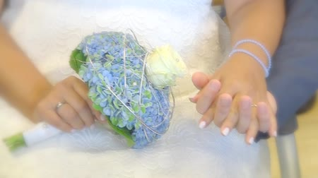 pearl : Bride and groom keeps their hands on a bridal bouquet and ring Stock Footage