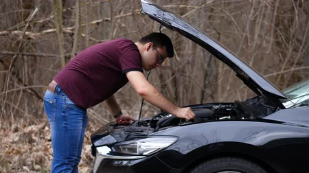 triângulo : A man is trying to repair a broken car Stock Footage
