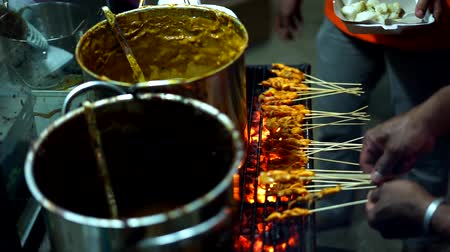 night singapore : Satay Padang, Meat skewers cook over hot coals at Indonesian Street food market Stock Footage
