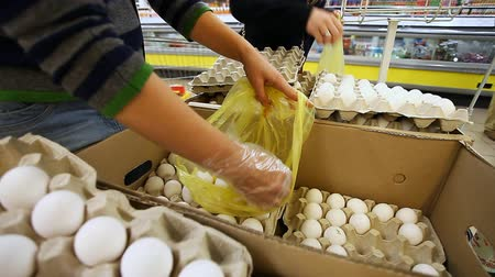 casca de ovo : woman buys eggs at the supermarket