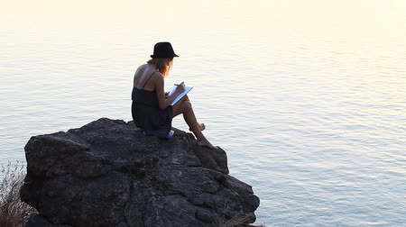 autor : creative personality with a notebook on the riverside during sunset