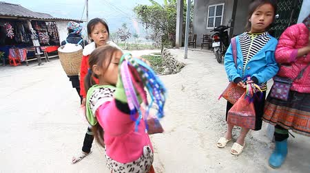minority group : Sapa, Vietnam - November 30, 2016 : Group of children persistently ask that tourists have bought their souvenirs.. Selling souvenirs is one of the main sources of income for Hmong