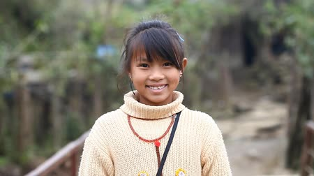 племенной : Sapa, Vietnam - November 30, 2016 : A little girl from the ethnic group of Hmong poses the foreigner for the camera. Children often pose for this purpose to earn reward or to sell the souvenirs.