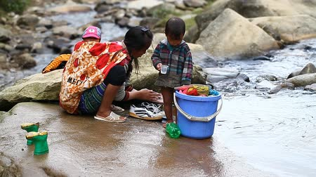 sapa people : Sapa, Vietnam - November 30, 2016 : A woman from the ethnic group of black Hmong washes clothes in the mountain river in the neighborhood of the village