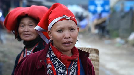 local : Sapa, Vietnam - November 30, 2016 : A woman from the ethnic group of red Dao in a national costume . Posing in front of tourists and selling souvenirs is one of the main sources of income for Hmong