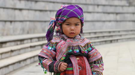 sapa people : Sapa, Vietnam - November 30, 2016 : A little girl from the ethnic group of Hmong in a national costume. Posing before tourists and selling souvenirs is one of the main sources of income for Hmong Stock Footage