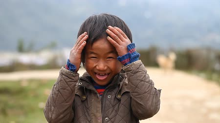 délkelet Ázsia : Sapa, Vietnam-December 01,2016:A charismatic boy belonging to ethnic minorities Hmong with pleasure grimaces and poses in front of a foreign camera.
