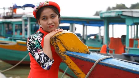 hoi an : Hoi An, Vietnam-December 28,2016: A sweet Vietnamese girl in a national dress was walking along the waterfront of Hoi An city. Stock Footage
