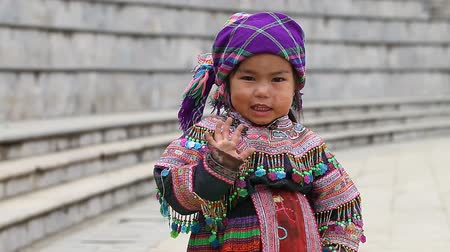 племенной : Sapa, Vietnam - November 30, 2016 : A little girl from the ethnic group of Hmong in a national costume. Posing before tourists and selling souvenirs is one of the main sources of income for Hmong Стоковые видеозаписи
