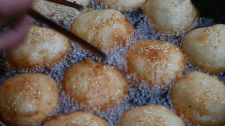 Asia. Asian street food. Fried donuts in oil Stock Footage