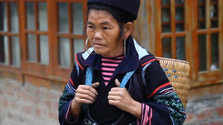 sapa people : Sapa, Vietnam - November 30, 2016 : A woman from the ethnic group of Hmong in a national costume . Posing in front of tourists and selling souvenirs is one of the main sources of income for Hmong