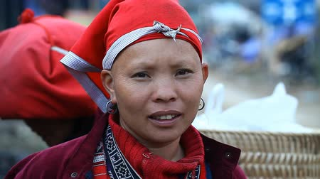 sell : Sapa, Vietnam - November 30, 2016 : A woman from the ethnic group of red Dao in a national costume . The shaved eyebrows and head hair mean that the girl is married.